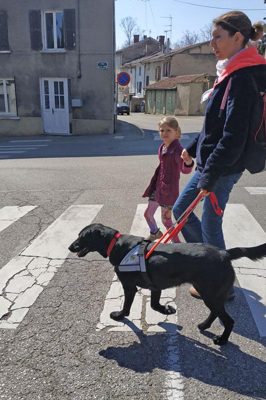 Alison guidée par son chien guide Moka