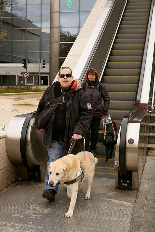 Virgile et Christelle au bas d'un escalator guidés par Dipsy et Jazzy.