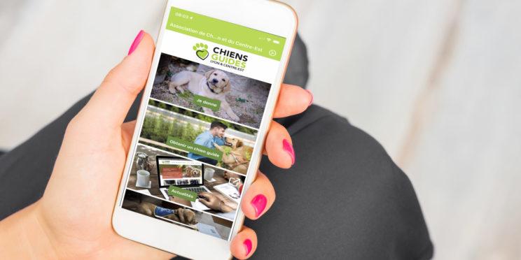 Une main de femme tient un smartphone qui affiche l'application des Chiens Guides de Lyon et du Centre-Est.
