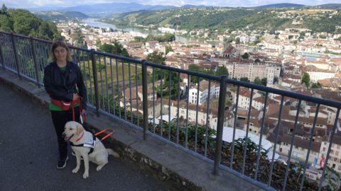Laurie avec Polka sa chienne sable au harnais et en arrière plan on domine la ville.